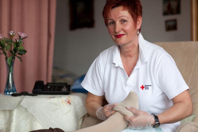 01 Deutsches Rotes Kreuz DRK, Einsatzbereiche / Aktivitaeten / Leistungen / Aufgaben, Sozialarbeit, Ambulante Pflege Hauspflege haeusliche Pflege, Strumpf, anziehen, Einmalhandschuhe, Betreuung